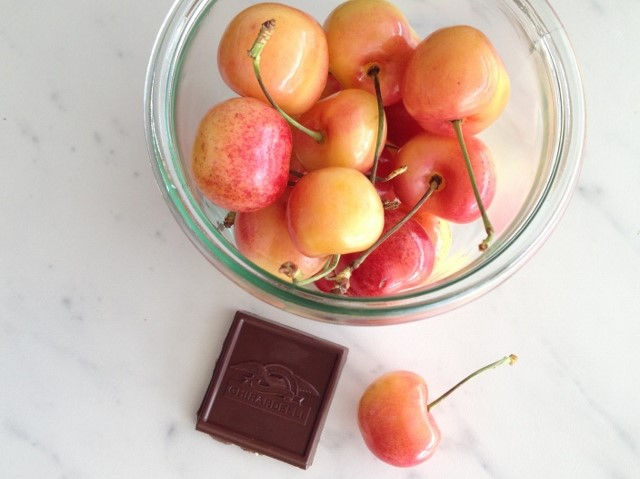 small jar filled with cherries next to 1 square of dark chocolate
