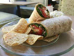Veggie wrap on a plate with chips
