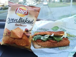 Subway sandwich and chips on car dashboard