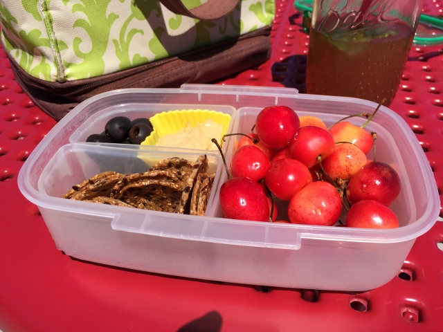 Cherries, crackers, olives, hummus bento lunch