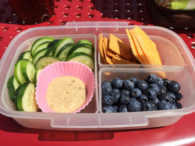 Cucumber, goddess dressing, cheese, crackers, blueberries bento lunch
