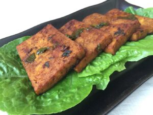 Pieces of cooked tofu on lettuce leaves on a rectangular plate