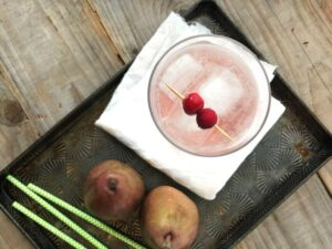Top down view of an iced pink drink next to straws and pears