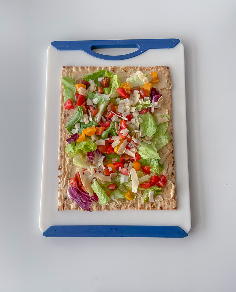 Top down view of a lavash bread covered with hummus and veggies