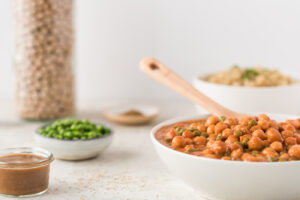 Bowl of garbanzo beans in tomato sauce with a wooden spoon to serve