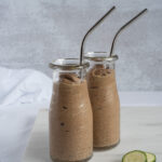Two small jars full of chocolate smoothie with straws