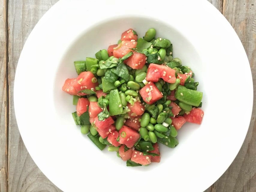 White bowl filled with watermelon, snap peas and edamame