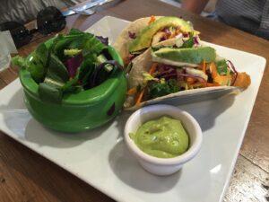 Bowl of salad alongside two vegetarian fish tacos