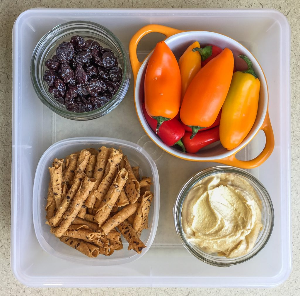 Healthy work snacks dried cherries, sweet peppers, hummus, tortilla chips