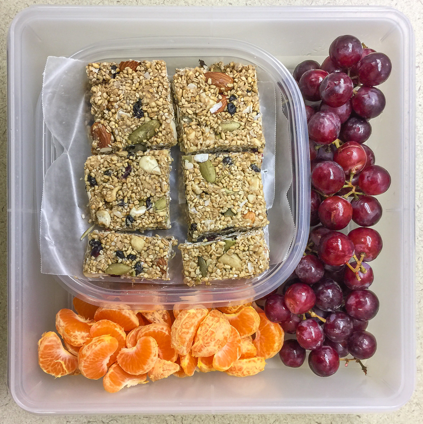 Healthy work snacks granola bars, grapes, mandarins