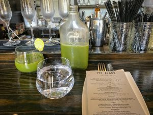 Bottle of green juice, glass of water and glass of juice on a bar