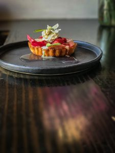 A round black plate with a small fruit tart topped with an edible flower