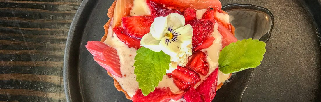 A round black plate with a strawberry rhubarb tart