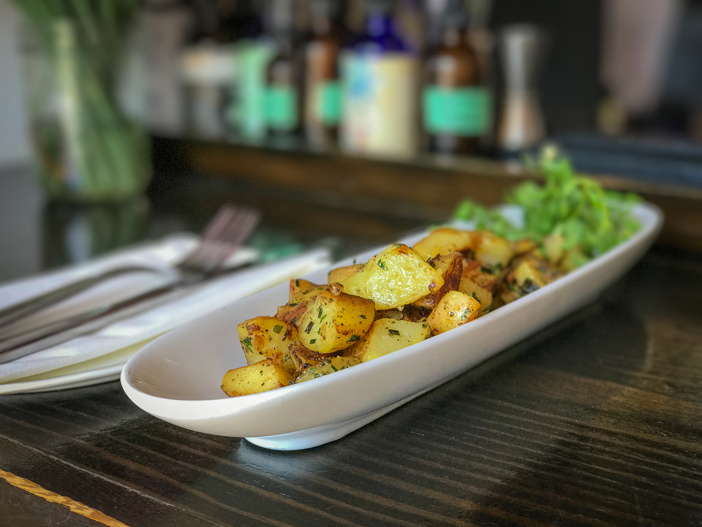 An oblong plate filled with roasted potatoes on a bar
