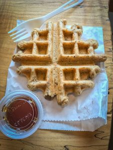A small waffle sitting on a paper sack, alongside a fork and a container of maple syrup