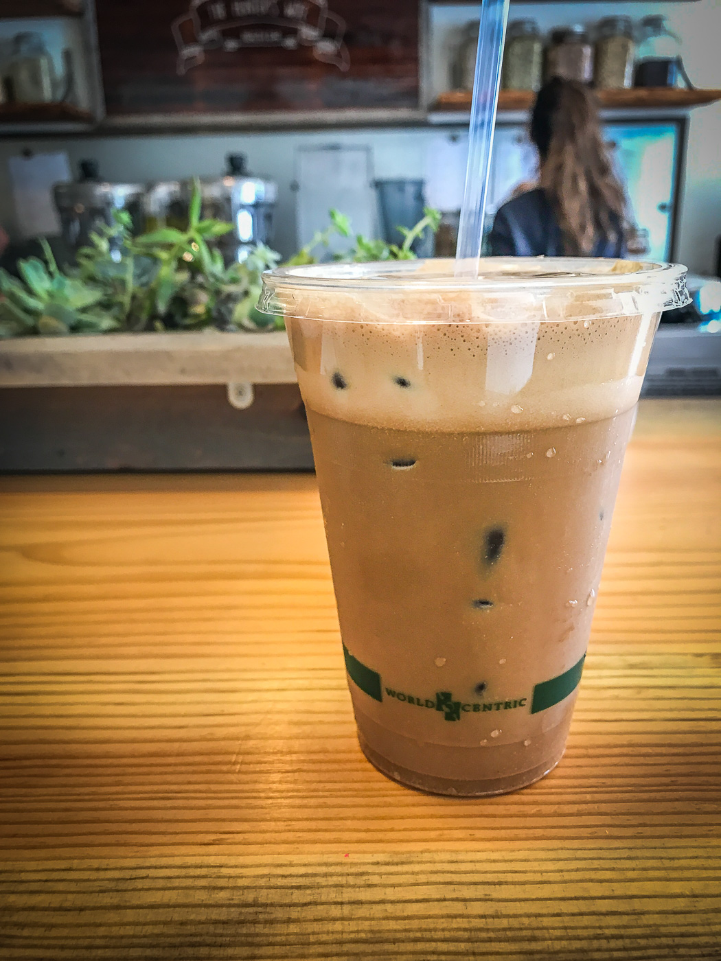 An iced coffee drink sitting on a wooden bar