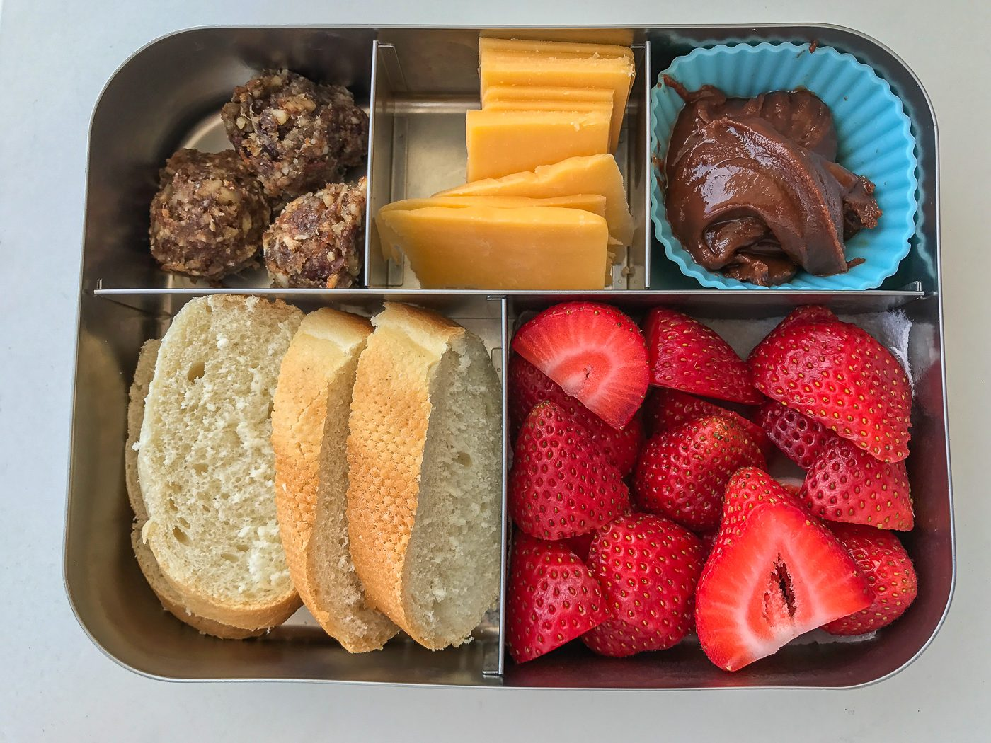 A bento lunch box filled with bread, strawberries, cheese, hazelnut spread and Unwrapp'd dough balls