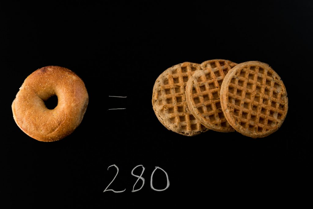 A whole wheat bagel and three whole grain frozen waffles on a black background with the number 280 written below them