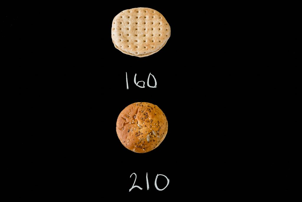 A sandwich thin and a hamburger bun on a black background with their calories listed (160, 210)