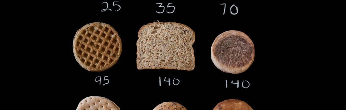 Black background with 9 different breads laid out with calorie values