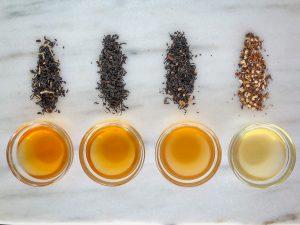 5 cups of brewed tea next to piles of loose tea
