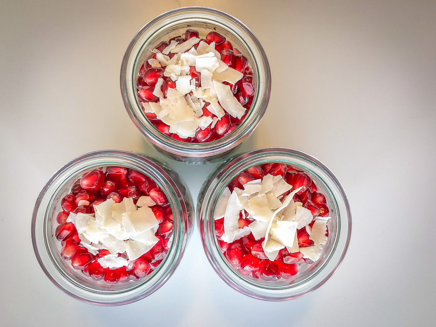 Three Weck jars filled with chia pudding and pomegranate