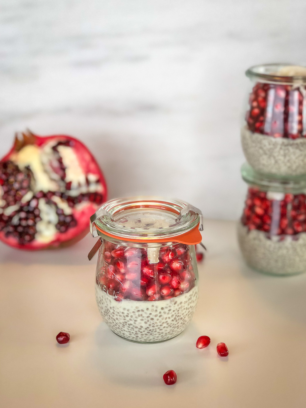One close up jar of chia pudding with a pomegranate and more jars in the background