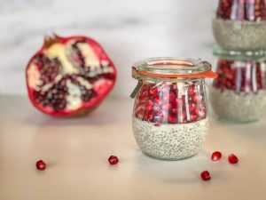 Coconut Chia Pudding in Weck jar surrounded by pomegranate arils