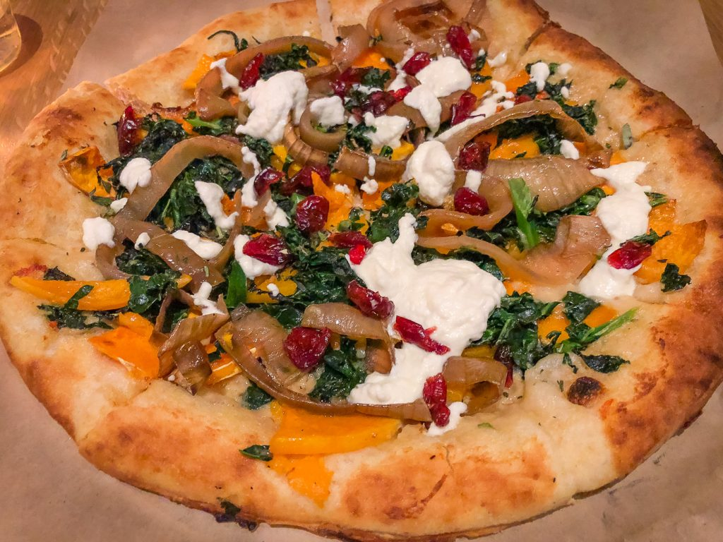 A pizza topped with onions, squash, ricotta and dried cranberries