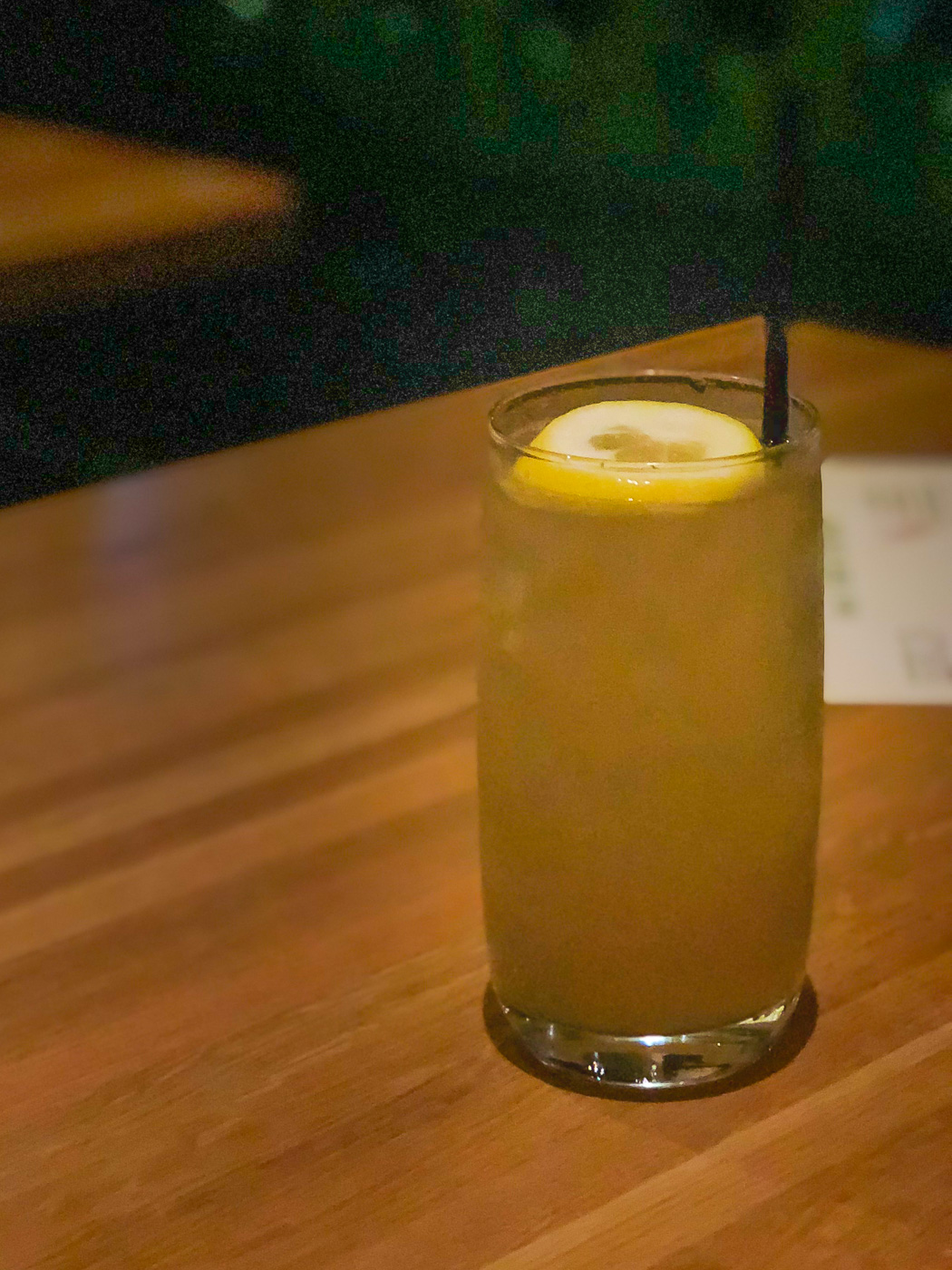 A glass of iced tea garnished with lemon and a straw on a wooden table