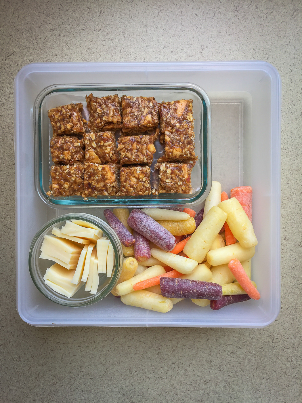 Square plastic container with granola bars, baby carrots, and mozzarella cheese
