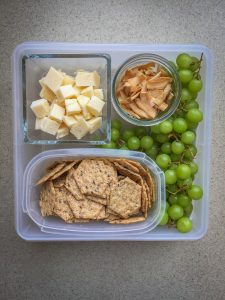 Plastic container with cheese, coconut chips, grapes, and multigrain crackers