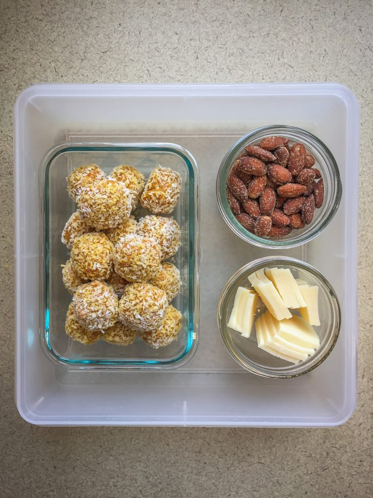 Plastic container with energy balls, almonds and cheese