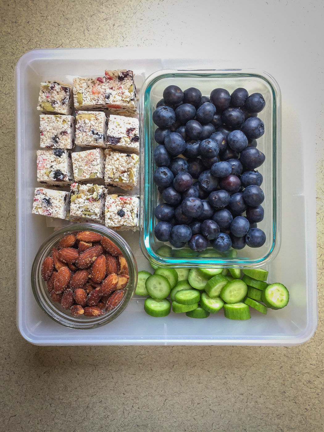 Square plastic container with blueberries, coconut bites, cucumber slices and almonds