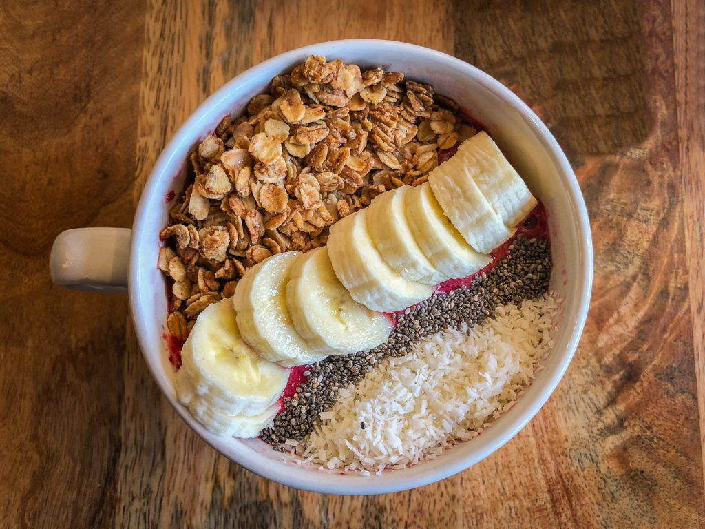 White ceramic bowl filled with red smoothie and topped with granola, coconut, banana, and chia seeds