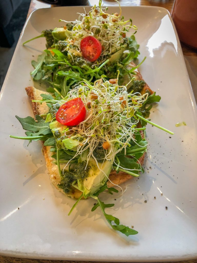 White rectangular plate with toast topped with sprouts, tomato and avocado
