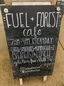 Chalkboard sandwich board sign with Fuel + Forest written on it