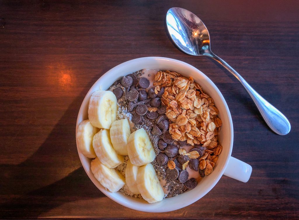 Large white mug filled with smoothie topped with banana, chia seeds, chocolate chips and granola next to a spoon