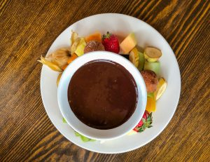 Top down photo of a plate of fruit and donut holes surrounding a fondue pot of chocolate