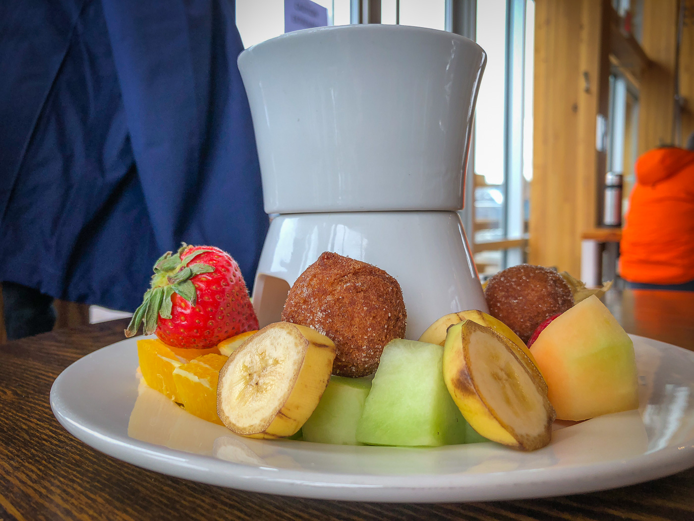 Side shot of a small pot of chocolate fondue surrounded by banana slices, berries, and melon