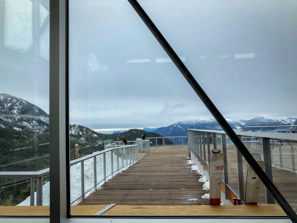 A patio with railing outside a mountaintop lodge