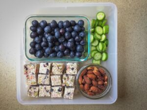 Tupperware filled with blueberries, nuts, and veggies