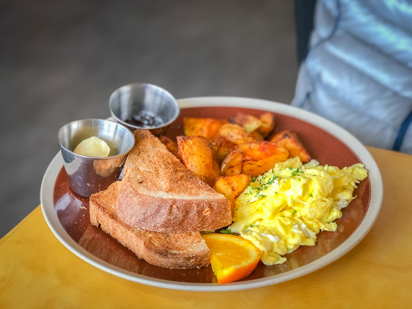Brown plate with scrambled eggs, whole wheat toast, and roasted potatoes