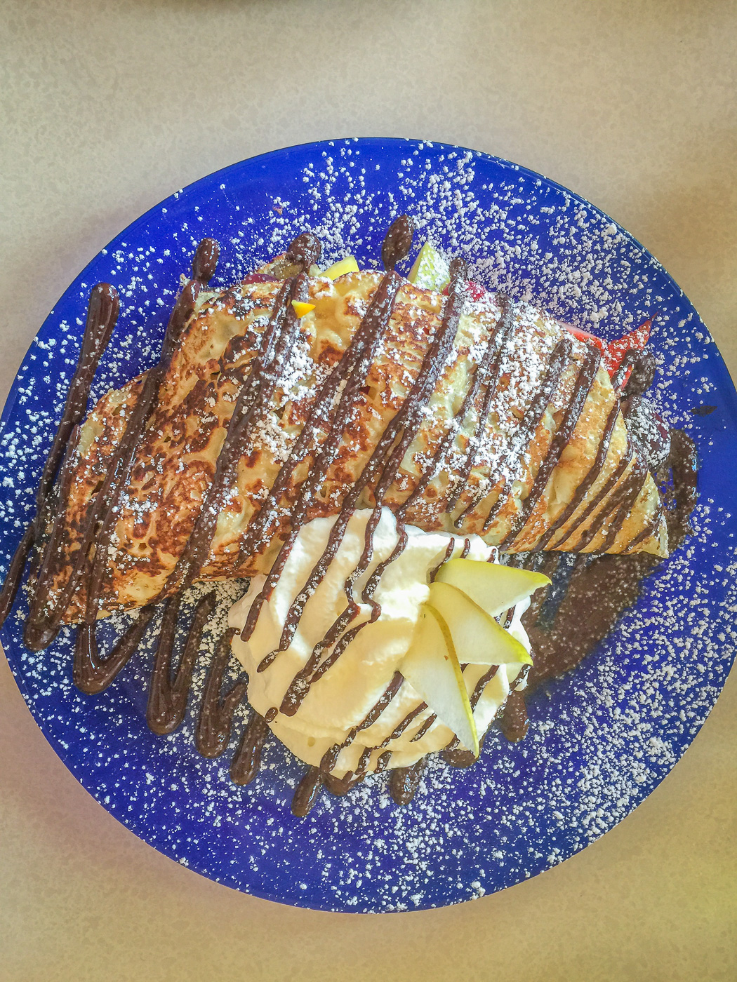 Blue plate with crepe and whipped cream drizzled with chocolate