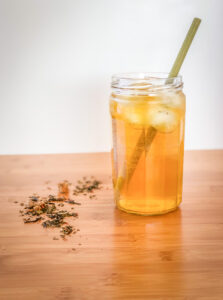 Glass filled with iced tea and a straw on a counter