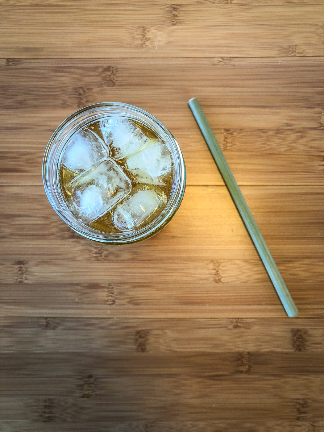 Top down photo of glass filled with iced tea and ice next to a bamboo straw