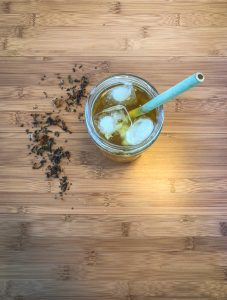 Top down photo of glass with iced tea with some loose leaf tea sprinkled next to it