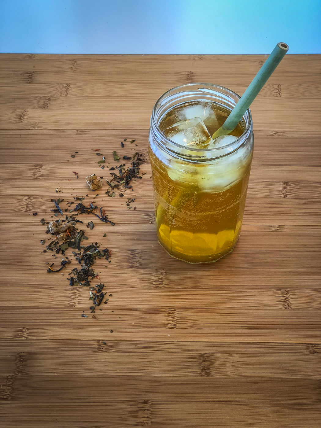 Glass of iced tea with a straw, with some loose leaf tea sprinkled next to it