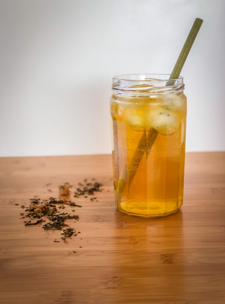 Side view of a glass of iced tea with a bamboo straw and loose leaf tea sprinkled next to it