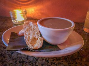 Bowl of soup on a plate with a napkin and two pieces of baguette with melted parmesan